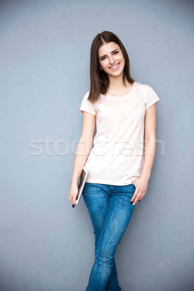 Cheerful young woman holding tablet computer over gray background Stock photo © deandrobot