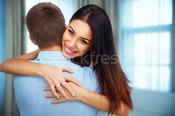 Portrait of a happiness woman hugging his boyfriend at home Stock photo © deandrobot