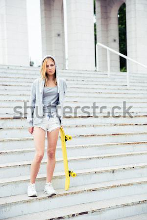 Lány rövidnadrág tart gördeszka kint hátsó nézet Stock fotó © deandrobot