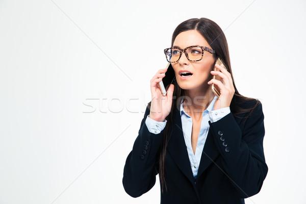 Businesswoman talking on two phones Stock photo © deandrobot
