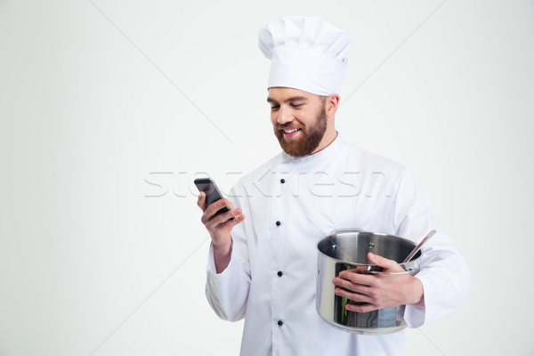 Male chef cook holding pot and using smartphone Stock photo © deandrobot