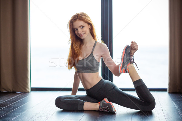 Fitness redhair woman stretching legs  Stock photo © deandrobot
