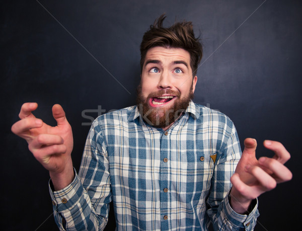 Ugly bearded man grimacing over black background Stock photo © deandrobot
