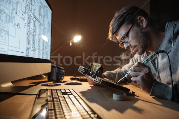 Focused man repairing motheboard with soldering iron  Stock photo © deandrobot