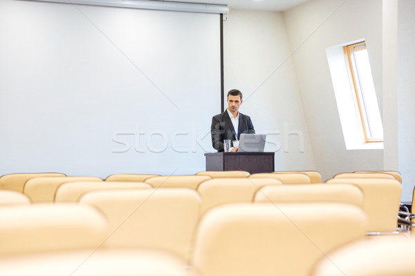 Thoughtful businessman with laptop in empty conference hall Stock photo © deandrobot