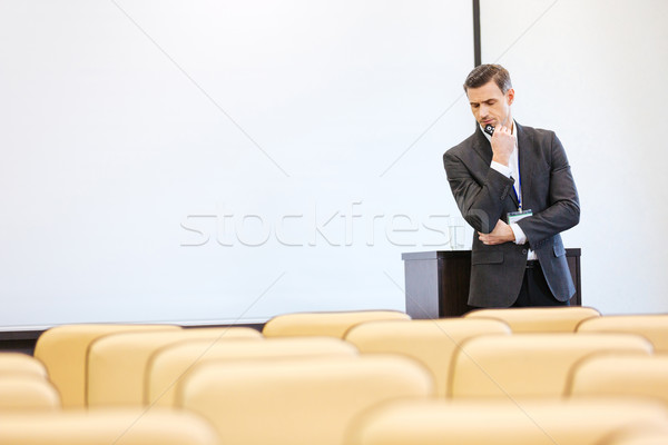 Thoughtful businessman standing in empty conference hall Stock photo © deandrobot