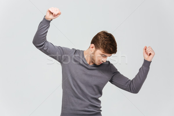 Attractive young man in grey pullover dancing Stock photo © deandrobot