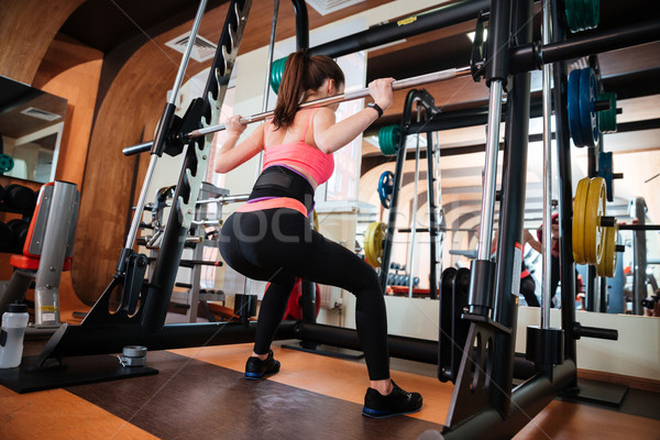 Attractive young sportswoman doing squats with barbell in gym Stock photo © deandrobot