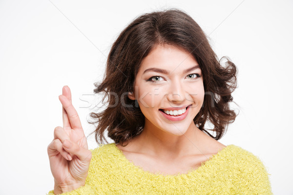 Smiling woman standing with crossed fingers  Stock photo © deandrobot