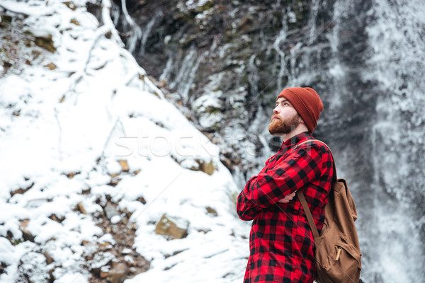 Man standing with arms crossed near mountain waterfall in winter Stock photo © deandrobot