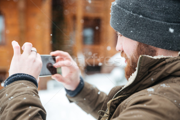 Man taking pictures with cell phone in snowy weather Stock photo © deandrobot