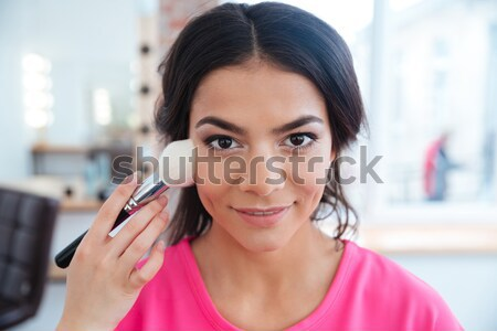 Woman doing professional makeup to happy beautiful young model  Stock photo © deandrobot
