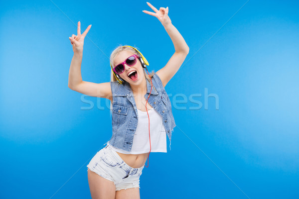 Cheerful stylish woman showing peace sign Stock photo © deandrobot