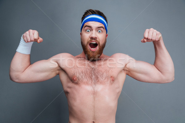 Happy amazed young sportsman standing and showing biceps Stock photo © deandrobot