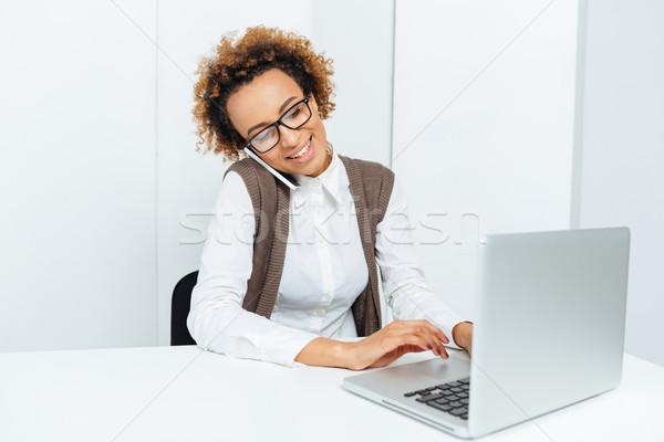 Сток-фото: улыбаясь · африканских · деловая · женщина · используя · ноутбук · говорить · сотового · телефона
