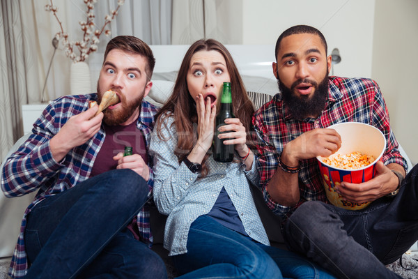 Frightened shocked people drinking beer and watching tv Stock photo © deandrobot