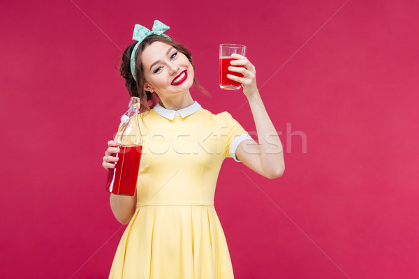 Smiling pretty pinup girl holding bottle and glass of juice Stock photo © deandrobot