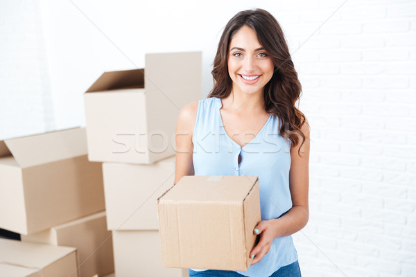 Happy woman moving in carrying carton boxes Stock photo © deandrobot