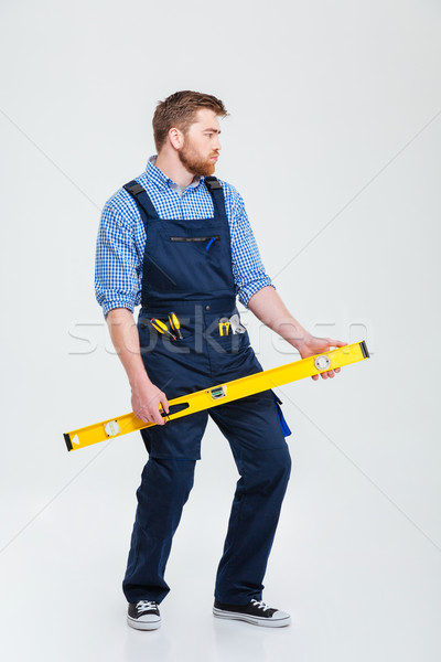 Funny male builder holding waterpas Stock photo © deandrobot