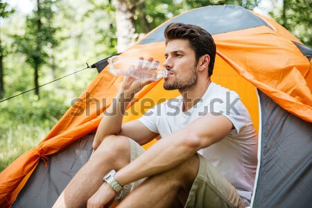 Man tourist with binoculars sitting near touristic tent in forest Stock photo © deandrobot