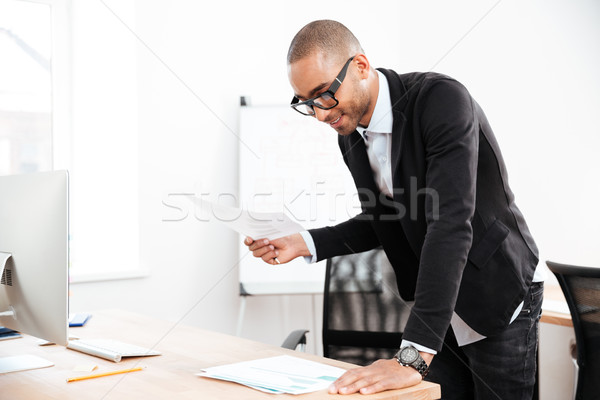 Businessman watching at statistics in a paper document Stock photo © deandrobot
