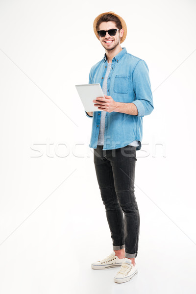 Stockfoto: Glimlachend · jonge · man · zonnebril · hoed · tablet