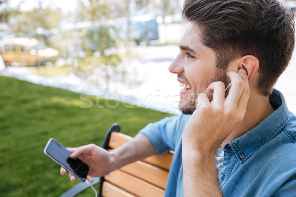 Close-up portrait of a young man sitting with mobilephone Stock photo © deandrobot