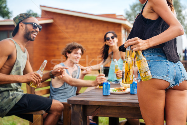 Group of teenage friends drinking beer and eating snacks Stock photo © deandrobot
