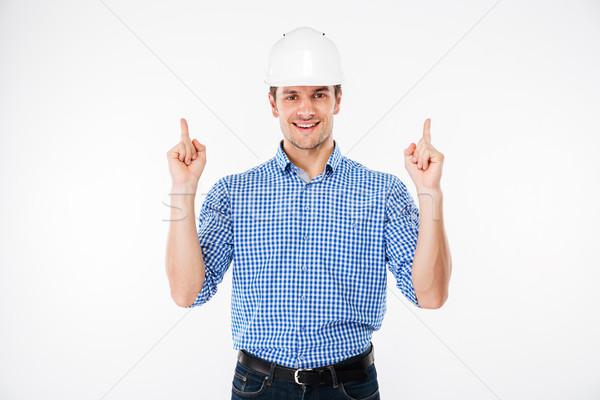 若い男 ビルダー ヘルメット ポインティング アップ ストックフォト © deandrobot