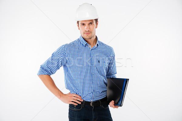 Handsome young man building engineer in helmet with folder Stock photo © deandrobot