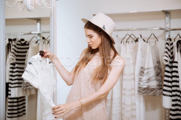 Zamyślony młoda kobieta patrząc sukienka showroom Zdjęcia stock © deandrobot