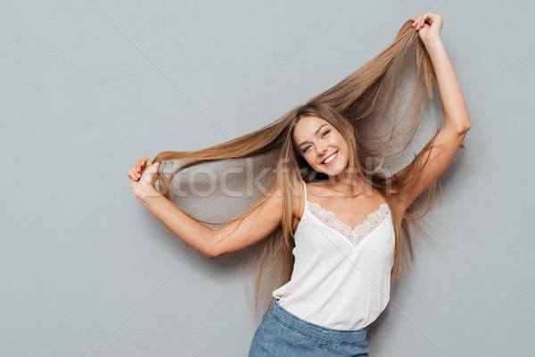 Young beautiful smiling girl with long hair posing Stock photo © deandrobot