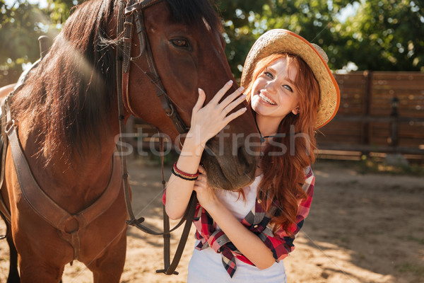 Happy woman cowgirl in hat standing and hugging her horse Stock photo © deandrobot