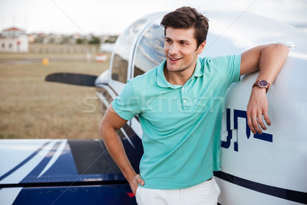 Happy man standing in field near small private airplane Stock photo © deandrobot