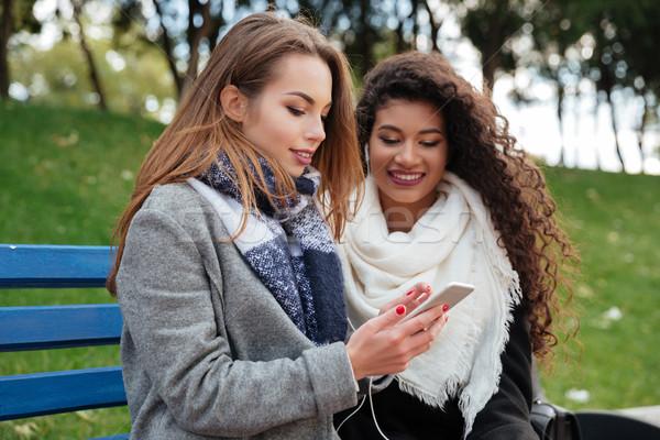 Hermosa las mujeres jóvenes sesión banco escuchar música Foto stock © deandrobot