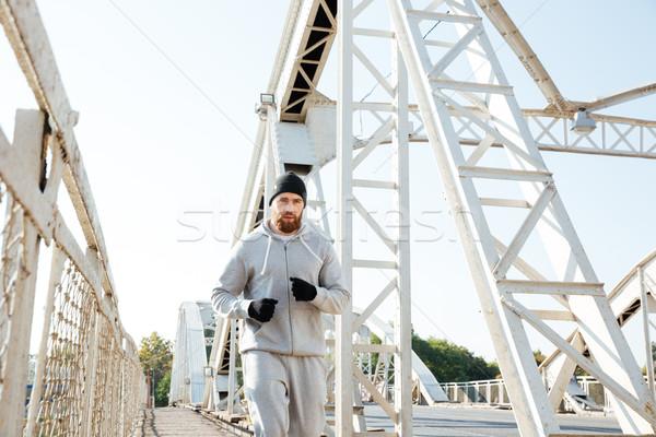 Attractive young bearded sportsman running across the bridge Stock photo © deandrobot