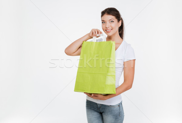 Woman holding purchasing after shopping and showing it to camera Stock photo © deandrobot