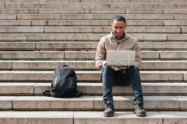 Happy african man sitting on staircase while using laptop Stock photo © deandrobot