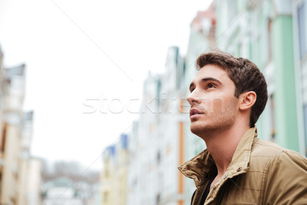 Attractive young man walking on the street Stock photo © deandrobot