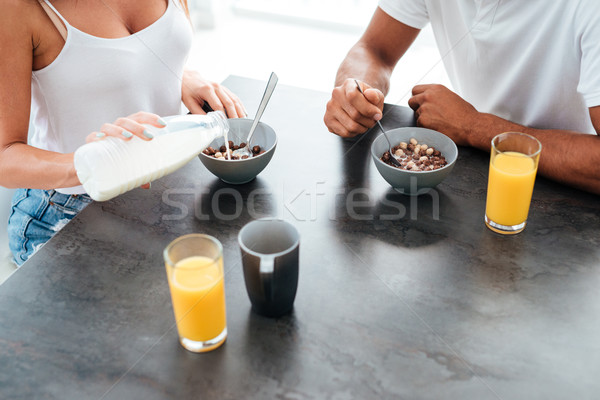 Couple eating cereals with milk for breakfast on the kitchen Stock photo © deandrobot