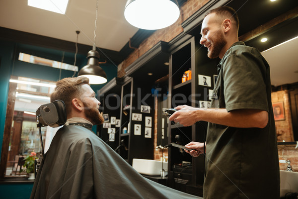 Happy man getting haircut by hairdresser with electric razor Stock photo © deandrobot