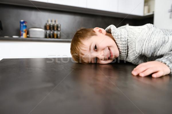 Mały szczęśliwy dziecko leży stół kuchenny Zdjęcia stock © deandrobot
