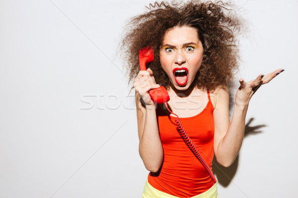 Evil Unusual model screaming at handset Stock photo © deandrobot