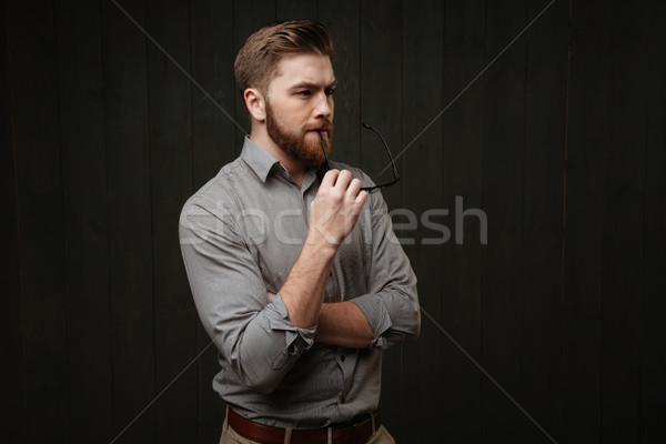 Pensive bearded man in shirt holding eyeglasses and looking away Stock photo © deandrobot