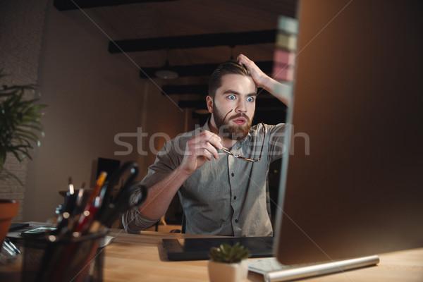 Handsome shocked web designer looking at computer. Stock photo © deandrobot