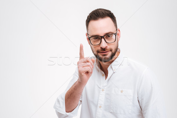 Concentrated young bearded man pointing Stock photo © deandrobot