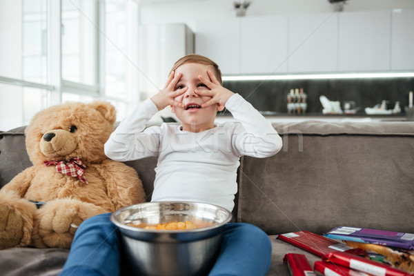 Scared boy on sofa with teddy bear watching TV Stock photo © deandrobot