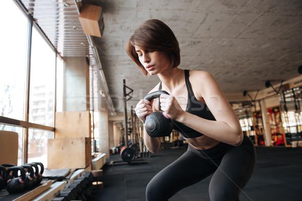 Fitnessz nő kettlebell tornaterem csinos fiatal nő Stock fotó © deandrobot