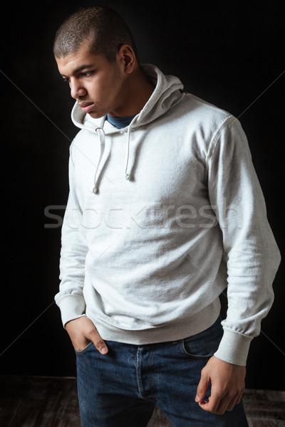 Déprimée africaine jeune homme permanent pense Photo stock © deandrobot