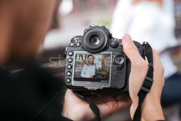 Photo camera holded by man photographer taking photos of woman Stock photo © deandrobot